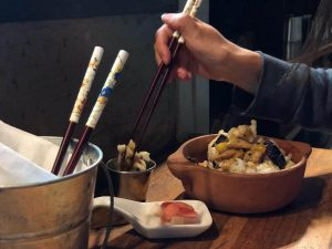 a hand reaching with a set of chopsticks for some food